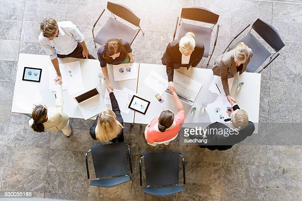Overhead view of business team meeting clients at desk in office