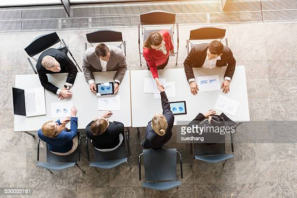 Overhead view of business team shaking hands with client at desk in office