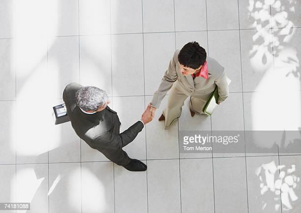 Vista aérea del Ejecutivo y ejecutiva estrechándose las manos