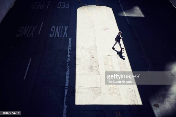 overhead view of businessman crossing street - schaduw stockfoto's en -beelden