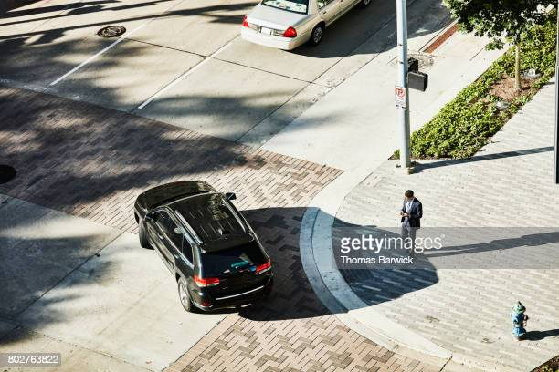 Overhead view of businessman on downtown street corner checking smartphone