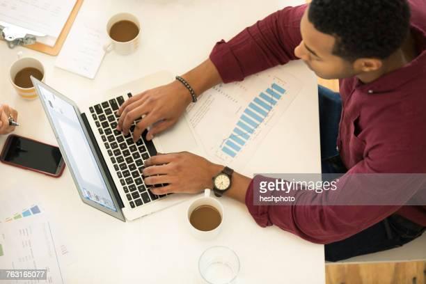 overhead view of businessman typing on laptop at desk - heshphoto stock-fotos und bilder