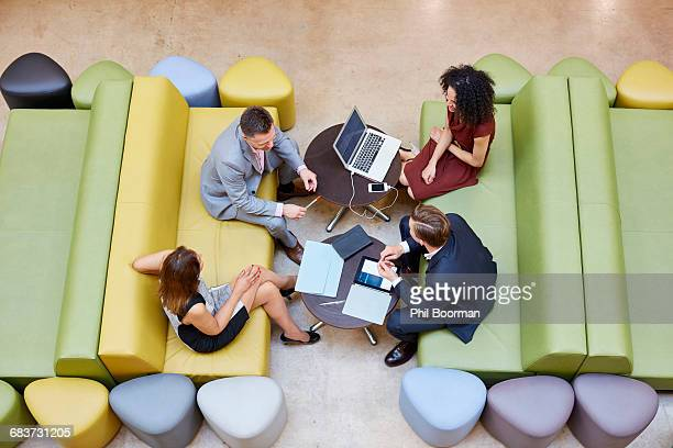 Overhead view of businessmen and businesswomen meeting on design studio sofas