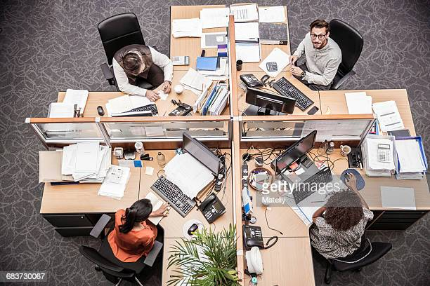 overhead view of businessmen and women at office desk - office cubicle stock pictures, royalty-free photos & images