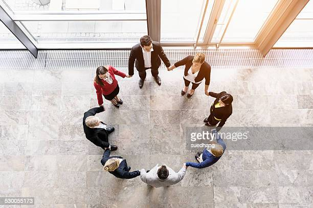 Overhead view of businessmen and women in circle holding hands