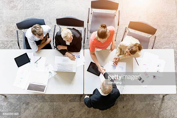 Overhead view of businessmen and women shaking hands with client at desk in office
