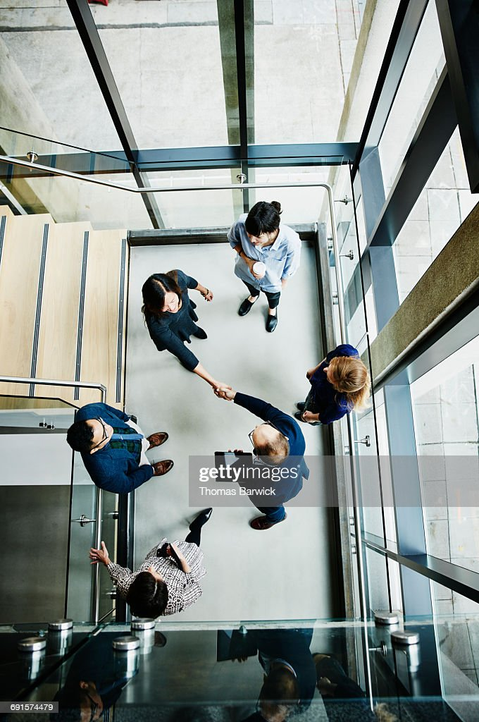 Overhead view of businesspeople shaking hands : Stock Photo