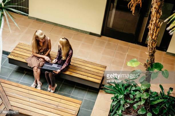 Overhead view of businesswomen talking in office courtyard