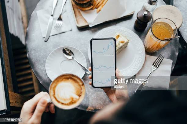 overhead view of busy businesswoman checking financial trading data with mobile app on smartphone in a coffee shop - blockchain stock pictures, royalty-free photos & images