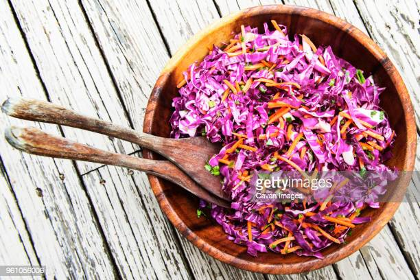 overhead view of cabbage and carrots salad served in bowl on wooden table - rodekool stockfoto's en -beelden