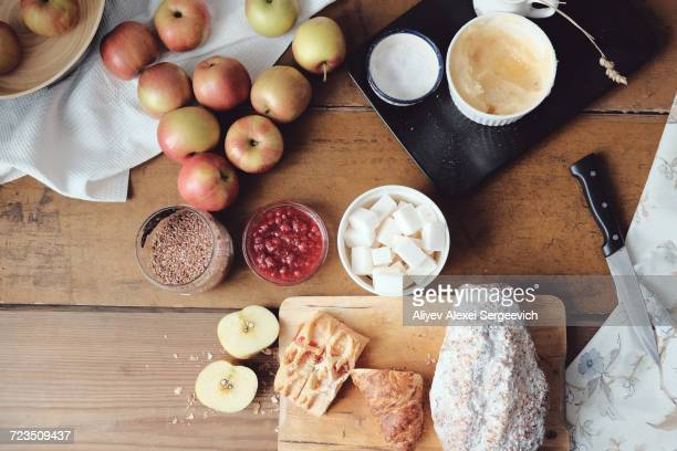 Overhead view of cake and desert ingredients with apples on kitchen table