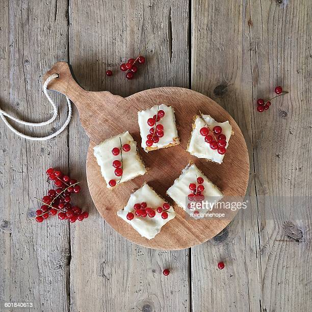 Overhead view of carrot cake with redcurrants on a chopping board