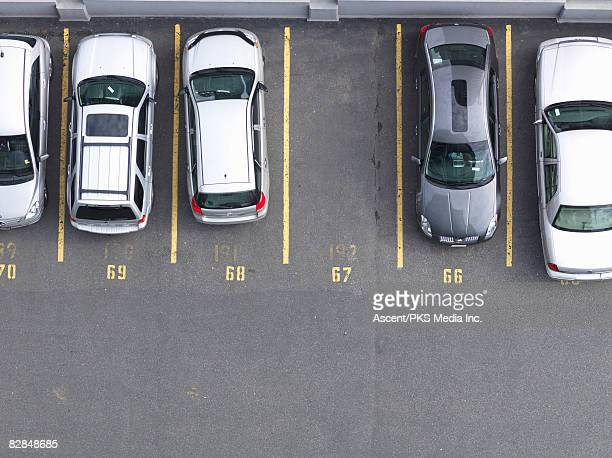 overhead view of cars in parking lot, one empty  - car park stock pictures, royalty-free photos & images