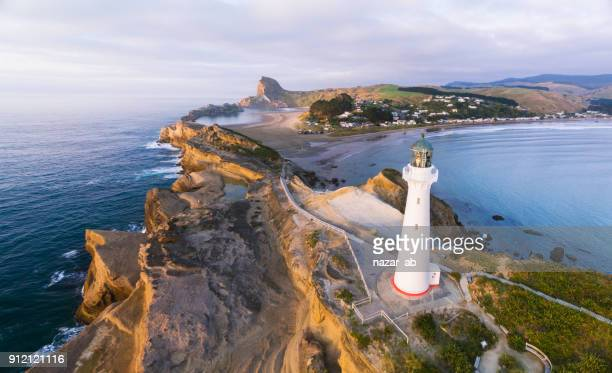 overhead view of castlepoint lighthouse with castlepoint village in background. - wellington new zealand stock photos and pictures