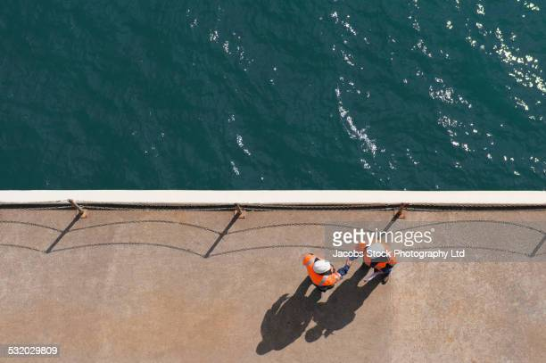 overhead view of caucasian technicians shaking hands near water - marine engineering stock pictures, royalty-free photos & images