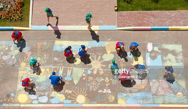 Overhead view of children drawing chalk pictures