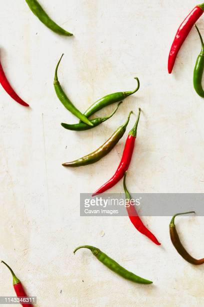 overhead view of chili peppers on white table - green chili pepper stock pictures, royalty-free photos & images