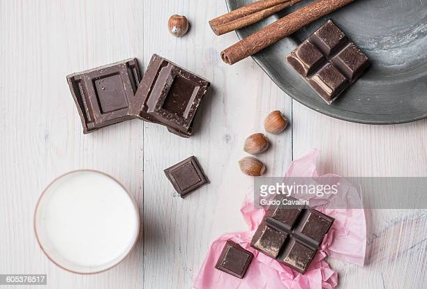 Overhead view of chocolate cubes, hazelnuts, cinnamon sticks, glass of milk