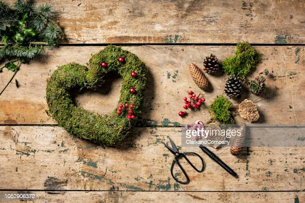 overhead view of christmas wreaths being made. - heart month stock photos and pictures