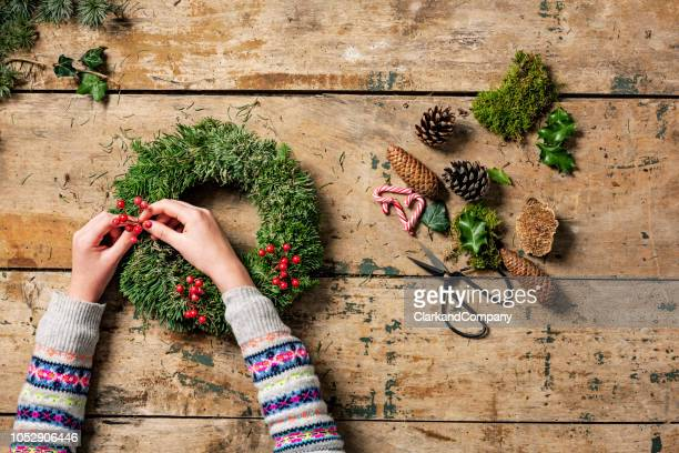 overhead view of christmas wreaths being made. - ornato foto e immagini stock