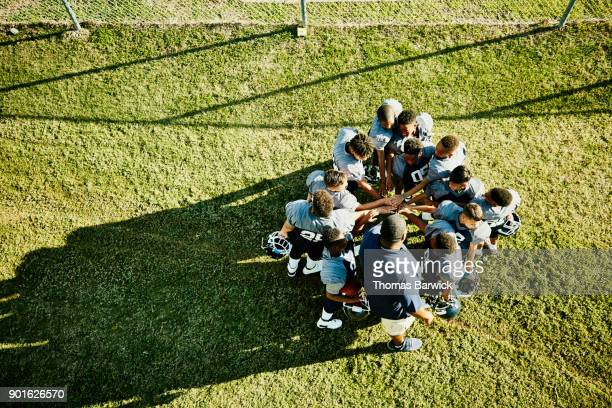 Overhead view of coach and football team gathered in circle with hands together before football game