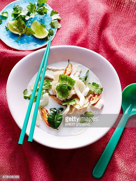 Overhead view of coconut milk hero tom kha in bowl with chopsticks and soup spoon