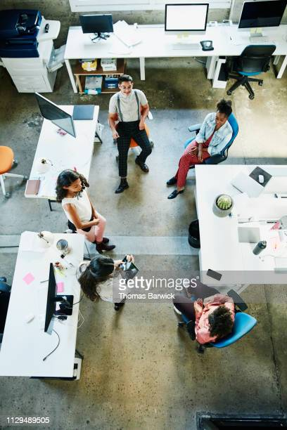 overhead view of colleagues having project meeting in design studio - studio workplace stock pictures, royalty-free photos & images