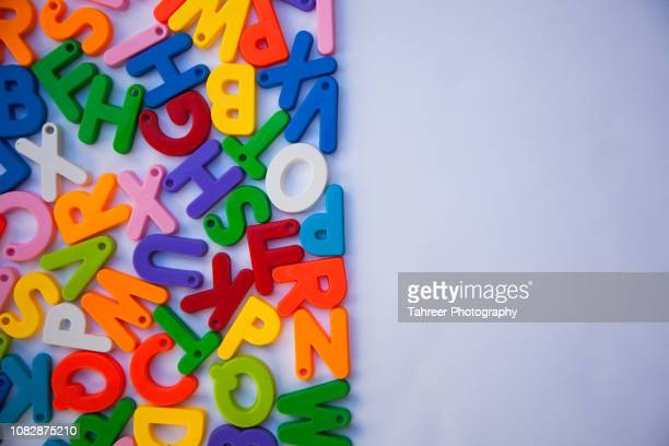 Overhead view of colorful alphabets arranged on white background