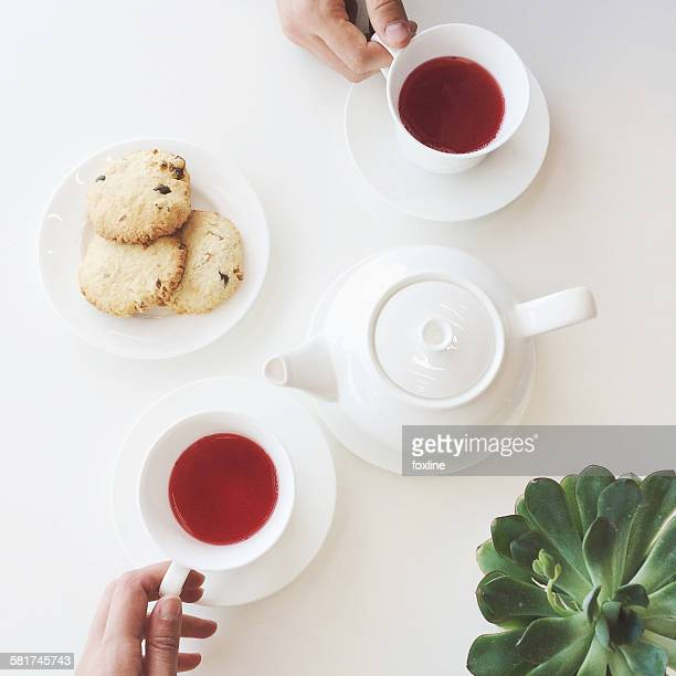 Overhead view of cookies and cups of tea