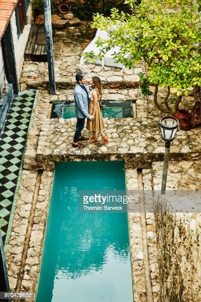 Overhead view of couple embracing on bridge over pool in courtyard of boutique hotel