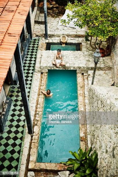 Overhead view of couple hanging out in courtyard pool of boutique hotel