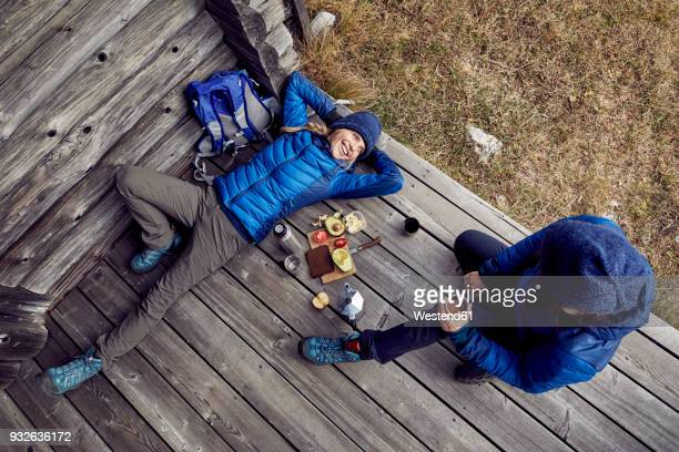 overhead view of couple hikers having a break at mountain hut - buitensport stockfoto's en -beelden