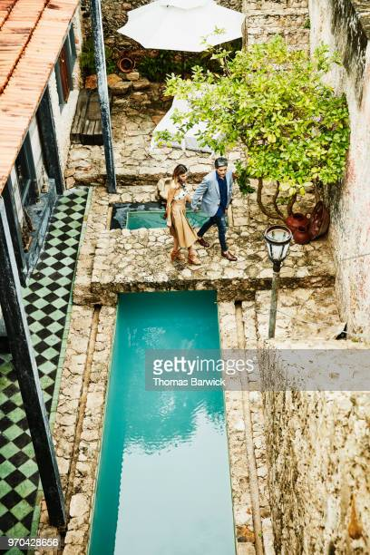 Overhead view of couple holding hands and walking across bridge over pool in courtyard of boutique hotel