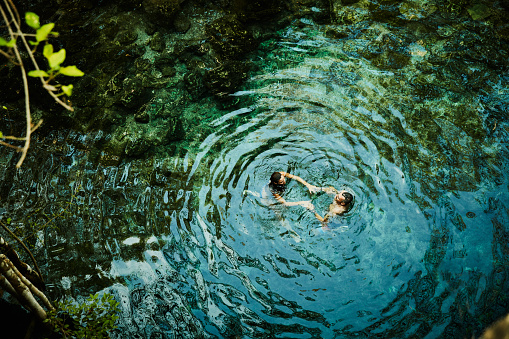Overhead view of couple holding hands while swimming in cenote during vacation - gettyimageskorea