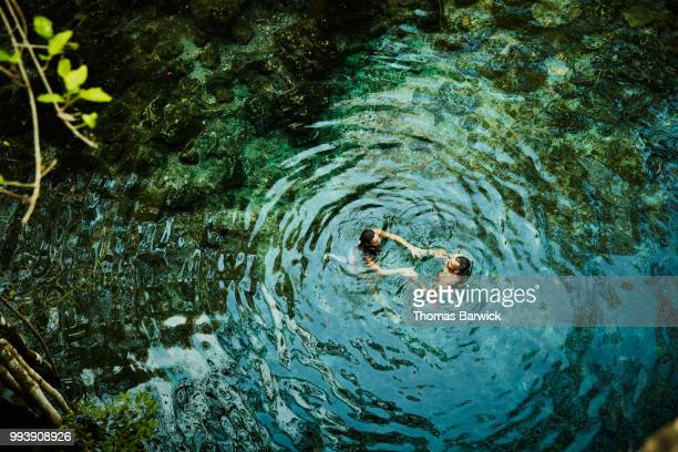 Overhead view of couple holding hands while swimming in cenote during vacation