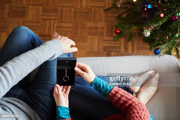 overhead view of couple holding xmas necklace gift on living room sofa - necklace stock pictures, royalty-free photos & images
