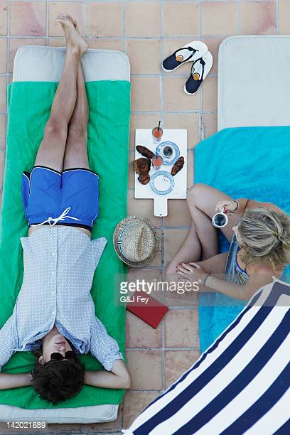 overhead view of couple in lawn chairs - girls sunbathing stock photos and pictures