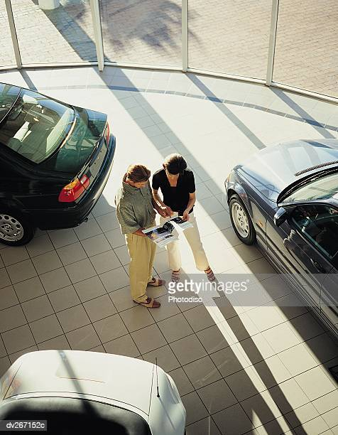 Overhead view of couple looking at brochure in showroom