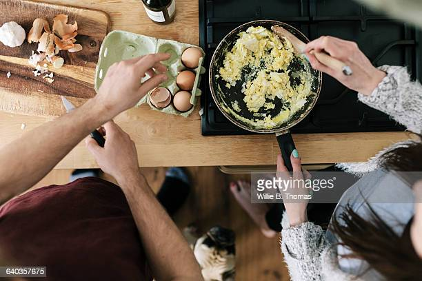 overhead view of couple making eggs - cooking utensil stock pictures, royalty-free photos & images