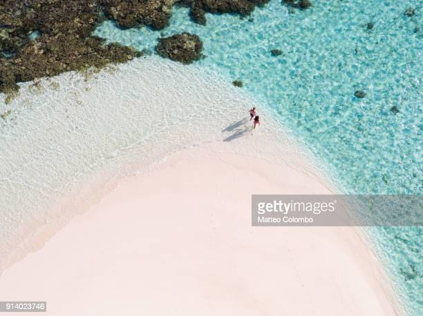 overhead view of couple on a beach, maldives - escapism stock photos and pictures