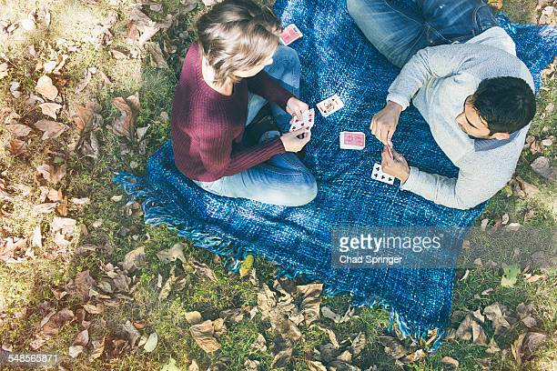 Overhead view of couple playing cards on blanket in forest