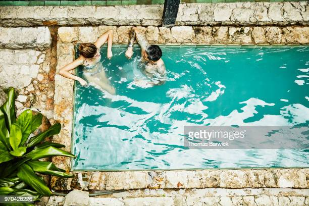Overhead view of couple relaxing together in hotel courtyard pool