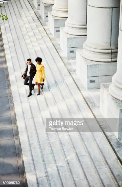 overhead view of couple walking down steps of building - yellow blazer stock photos and pictures
