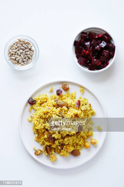 overhead view of couscous served in plate with beetroot salad and seeds in bowls on white background - couscous stock pictures, royalty-free photos & images