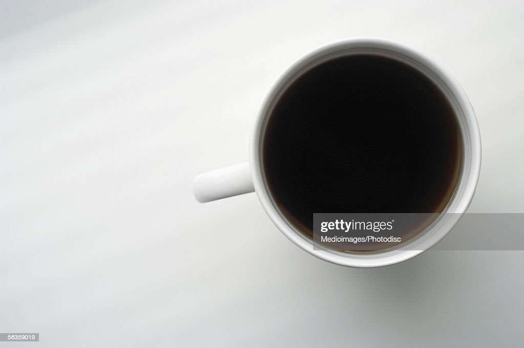 Overhead view of cup of black coffee on white surface : Stock Photo