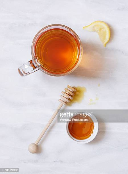 Overhead view of cup of tea and bowl of honey on marble table