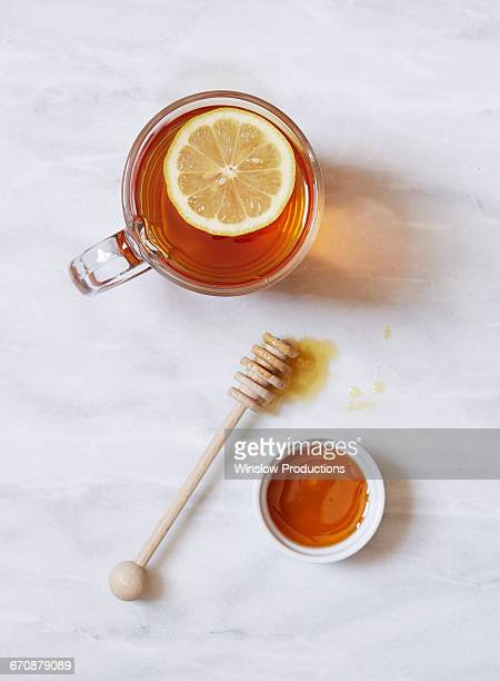 Overhead view of cup of tea with lemon and bowl of honey on marble table