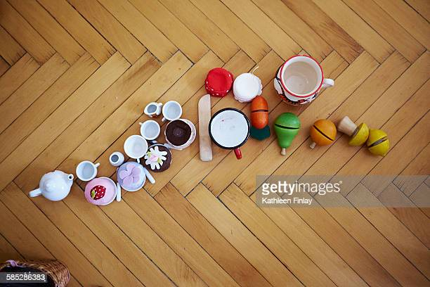 Overhead view of cupcakes, toys and cups on parquet floor