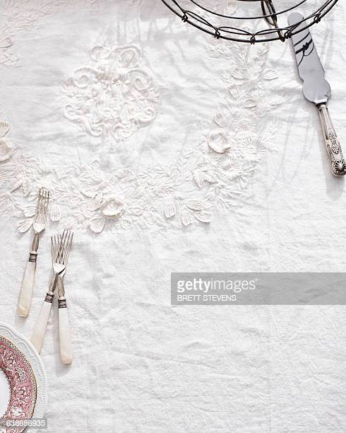 Overhead view of cutlery on white traditional tea tablecloth