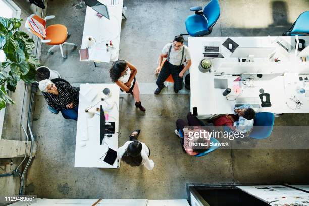 overhead view of design team having project meeting in office - business stockfoto's en -beelden
